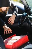 Burglar thief stealing smartphone and bag from car Royalty Free Stock Images