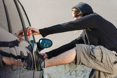 Thieft man holding screwdriver breaking into car Royalty Free Stock Photography