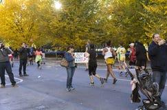 Anti-trumfkvinnan rymmer ut tecknet till löpare som deltar i NY royaltyfria foton