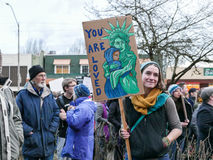 Anti-Trump demonstrator holds emotional Statue of Liberty sign at Oregon rally stock image