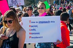 Anti-Trump messages at the 2018 Women`s March in Santa Ana. Santa Ana, California - January 20, 2018: Women holding an anti-Trump signs at the 2018 Women`s Royalty Free Stock Photography