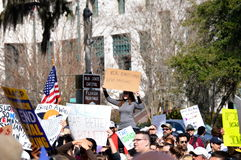 Anti-Trump Protest Tallahassee, Florida. A protester climbs a pillar to see the speakers while holding her sign aloft Royalty Free Stock Photo