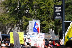 Anti-Trump Protest Tallahassee, Florida. Protest signs held up, including the muslim women with american flag head covering stock images