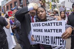 Anti-Trump protester with Black Lives Matter sign. SAN DIEGO, USA - MAY 27, 2016: A woman holds a Black Lives Matter sign while a Donald Trump impersonator Royalty Free Stock Image