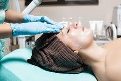 Anti-veroudert gezichtsmassage cosmetologist die massage voor jonge vrouw doen bij Kuuroordsalon stock foto's
