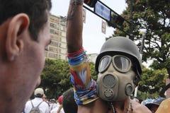 Anti vestir dos protestadores de Nicolas Maduro lança gás lacrimôgeneo a máscara durante as manifestações em massa que transforma fotografia de stock