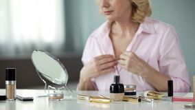 Anti-wrinkles products on table with senior woman looking neck in mirror, beauty. Stock photo royalty free stock photo