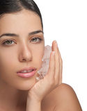 Antiaging Ice on Girl Face. Isolated photo of a girl holding ice cubes on her face to prevent aging. She applies ice to numb her toothache or for skincare Stock Photography