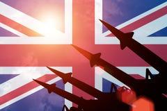 Antiaircraft rockets on background of United Kingdom flag. Antiaircraft rockets silhouettes on background of United Kingdom flag. Sunny royalty free stock photo