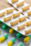 Antibiotic capsule drugs in the packaging on wood background. Stock Images
