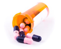 Antibiotics spilling out of a prescription bottle. On white background royalty free stock photo