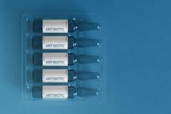 Antibiotika unter Verwendung des Konzeptes F?nf Ampules mit ?berlagerten Buchstaben von Aufschrift Antibiotikum Pharma-Biotechnol stockfotografie
