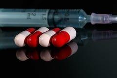 Antibiotiques et seringue rouges et roses photos stock