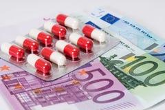 Antibiotiska kapslar i blåsa med eurosedlar Arkivfoton
