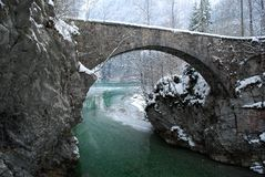 Antic bridge over a green river Stock Photo