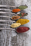 Antic metal spoons with different kinds of spices on old wooden Royalty Free Stock Images