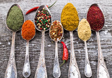 Antic metal spoons with different kinds of spices on old wooden Royalty Free Stock Photo