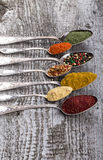 Antic metal spoons with different kinds of spices on old wooden Stock Images