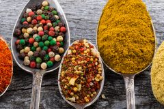 Antic metal spoons with different kinds of spices on old wooden Royalty Free Stock Photography