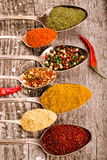 Antic metal spoons with different kinds of spices on old wooden Royalty Free Stock Image