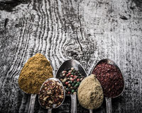 Antic metal spoons with different kinds of spices on old wooden Stock Image