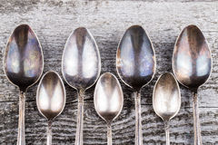 Antic metal spoons on old wooden board. Selective focus Stock Image