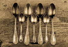 Antic metal spoons on old wooden board. Selective focus. Toned Stock Photo