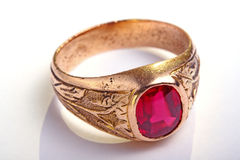 Antic ring, jewelry. Antic golden ring with ruby cabochon on white Royalty Free Stock Photo