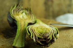 Sliced artichokes posed and lemon on background. An antichoke just sliced on an old cutboard waiting to be cooked in a tasty recipe Royalty Free Stock Photo