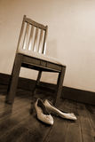 Anticipation. Shoes sit prepared for the days events in anticipation at the foot of a chair royalty free stock photo