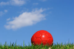 Anticipation. A red soccer ball against a blue sky Royalty Free Stock Photo