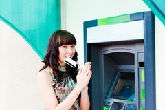 In anticipation of the money. Woman holds the teeth in the credit card Royalty Free Stock Photo