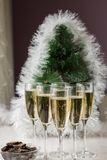 Champagne glasses and a New Year`s entourage with a Christmas tree, snowflakes are depicted. In anticipation of the New Year, freshly poured champagne glasses royalty free stock image