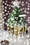 Champagne glasses and a New Year`s entourage with a Christmas tree, snowflakes are depicted. In anticipation of the New Year, freshly poured champagne glasses stock photography