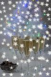 Champagne glasses and a New Year`s entourage with a Christmas tree, snowflakes are depicted. In anticipation of the New Year, freshly poured champagne glasses stock photos
