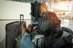 In anticipation of travel. Man who has a lot of bags, sits waiting for an airplane at the airport Royalty Free Stock Images