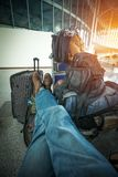 In anticipation of travel. Man who has a lot of bags, sits waiting for an airplane at the airport Royalty Free Stock Photography