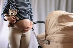 Anticiperen van moederschap Zwangere vrouw die zich dichtbij een kinderwagen bevinden royalty-vrije stock fotografie