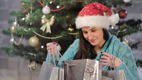 Anticipez le paquet de sourire et s'ouvrant européen de fête de femme de cadeau près de l'arbre de Noël décoré clips vidéos