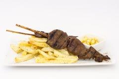 Anticuchos, cucina peruviana, carne infilzata grigliata del cuore del manzo con le patate delle fritture (patate fritte) Immagini Stock