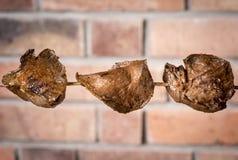 Anticuchos, peruanische Küche, Fleischherzkalbfleisch aufgespießt auf dem Grill mit dem Hintergrund einer Backsteinmauer lizenzfreie stockfotografie