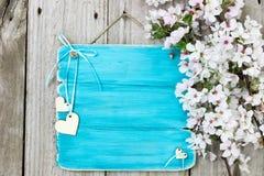 Antiek blauw teken met witte bloemen en houten harten die op houten omheining hangen Royalty-vrije Stock Afbeelding