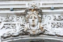 Antiek die gipspleistermasker en roestig op de voorgevel van het gebouw is gebarsten Het decor van een uitstekend huis vrouwelijk royalty-vrije stock fotografie