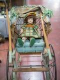 Antiek Doll met Groene en Oranje Kleding die op een Houten en Rieten Wandelwagen rusten stock foto
