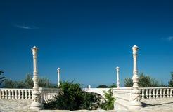 Antieke balustrade met ingang aan de tuin en duidelijke blauwe sk Stock Foto's