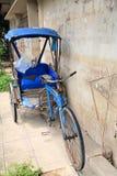 Antieke blauwe fiets met drie wielen stock foto