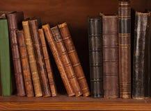 Antieke boeken op plank stock foto
