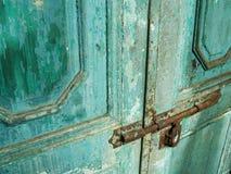 Antieke deur met afgebroken blauwe verf en geroest slot Stock Afbeelding