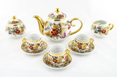 Antieke die porseleinthee en koffie met bloemmotief wordt geplaatst Stock Fotografie