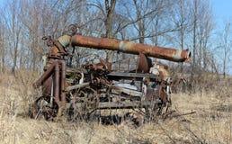 Antieke geselende machine die in het onkruid roesten Stock Foto's